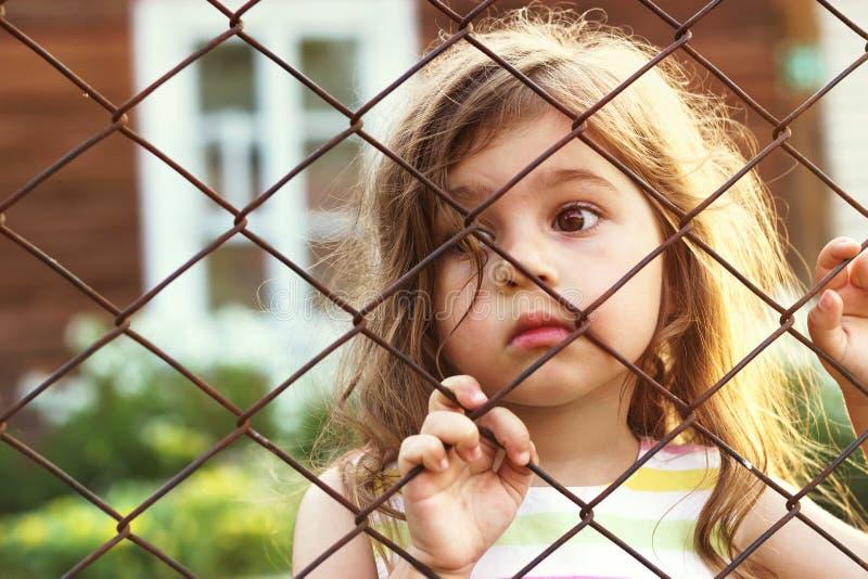 Getontes Porträt des traurigen netten kleinen Mädchens schaut durch Drahtzaun stockbilder