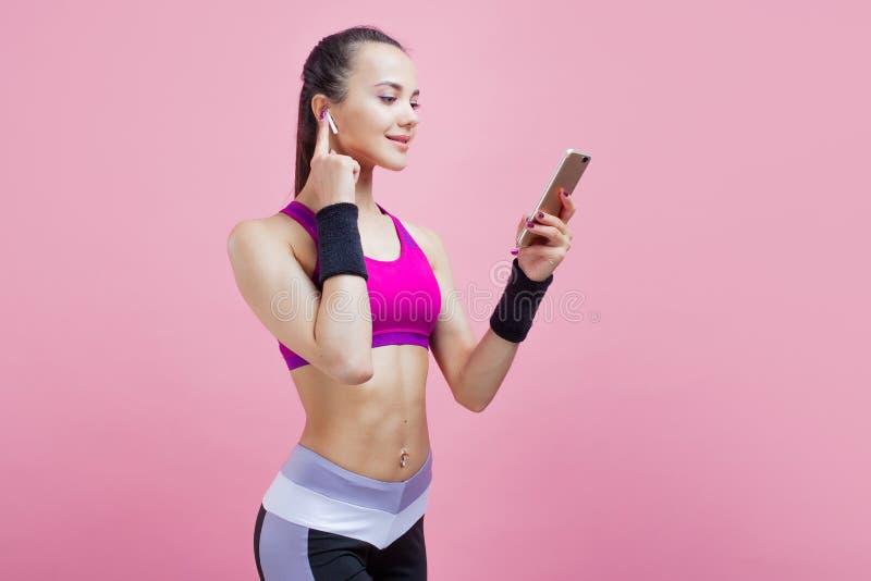 Getontes Wartetraining des jungen Brünettefrauenstand listenind on-line-Trainercouchsitzsportkleidungsgebrauchs-Handys stockbild