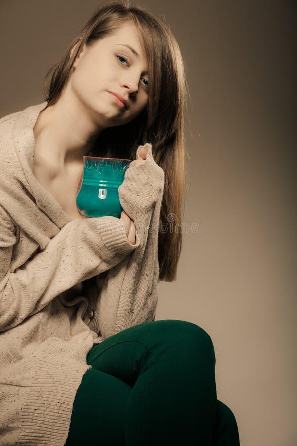 getränk Mädchen, das Schalenbecher heißen Getränktee oder -kaffee hält stockfotos