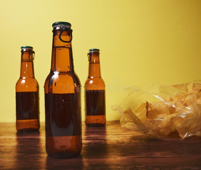 Getränk und Chips auf einem Holztisch und einem gelben Hintergrund lizenzfreie stockfotos