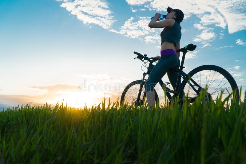 Getr?nkwasser w?hrend der Trainings sport Frau auf Fahrradsonnenuntergang stockbilder