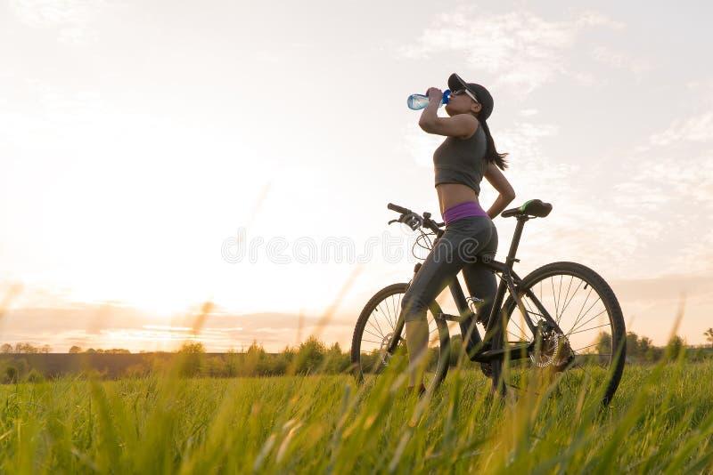 Getr?nkwasser w?hrend der Trainings sport Frau auf Fahrradsonnenuntergang lizenzfreies stockfoto