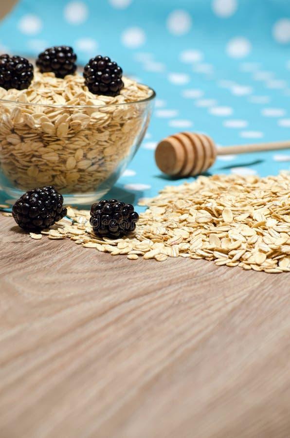 Getreide auf dem Tisch, Brombeeren und ein Löffel des Honigs stockfotografie