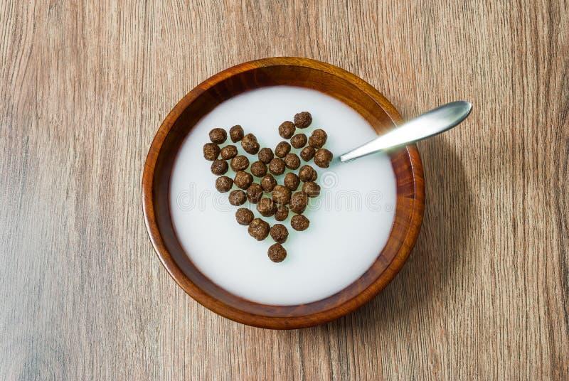 Getreide-Schokoladenbälle des Herzens geformte in der Milch stockfoto