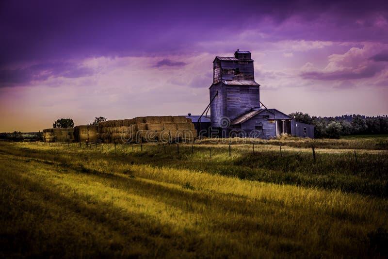 Getreideheber in der Landschaft mit Heukautionen stockfotos