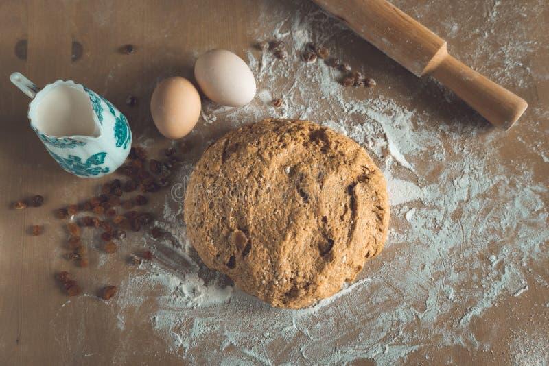 Getreidespeicherbrotteig mit Abstauben des Mehls und des Nudelholzes, der Eier und der Milch auf Holztisch in einem B?ckereiabsch stockfoto