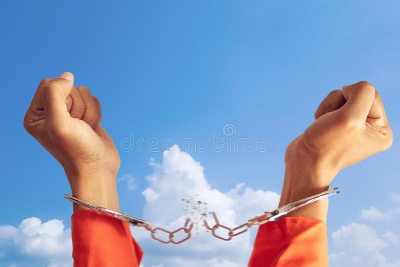 Getrennt auf Schwarzem zwei Hände des Gefangenen mit der defekten Handschelle für die Freiheit, die mit blauem Himmel am Hintergr stockfotografie