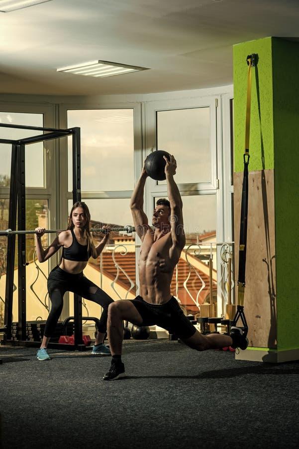 Getrennt auf Weiß Sportler, Athlet, muskulöser Macho trainiert mit trx Schleifen und Medizinball, Mädchen mit Barbell lizenzfreie stockfotografie