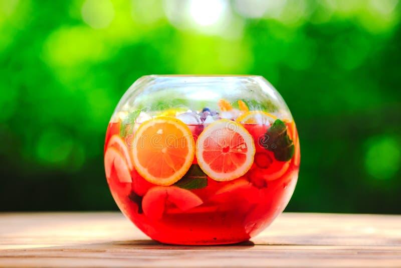 Getrennt auf Wei? Fruchtcocktail auf grünem Hintergrund Zitrusfrüchte, Beeren, Erdbeeren, Blaubeeren, Minze, Eis lizenzfreies stockfoto