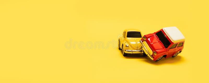 Getrennt auf Wei? Gelbe und rote Autos des Spielzeugs des Unfalles 2 auf einem gelben monophonischen Hintergrund stockfoto