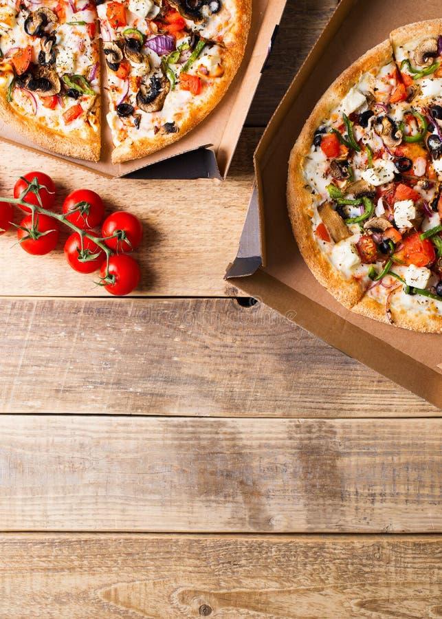 Getrennt auf Wei? Gemüsepizza in der offenen Pappschachtel auf Holztisch lizenzfreies stockbild