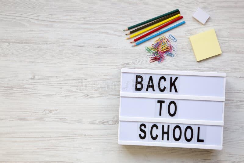 getrennte alte Bücher Radiergummi, Bleistifte, Aufkleber, Büroklammern und ` zurück zu Schule-` Wort auf einem modernen Brett übe stockbilder