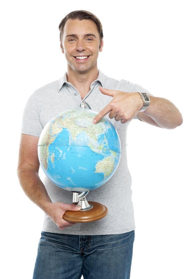 Getrennter junger Mann, der auf Kugel zeigt stockfoto