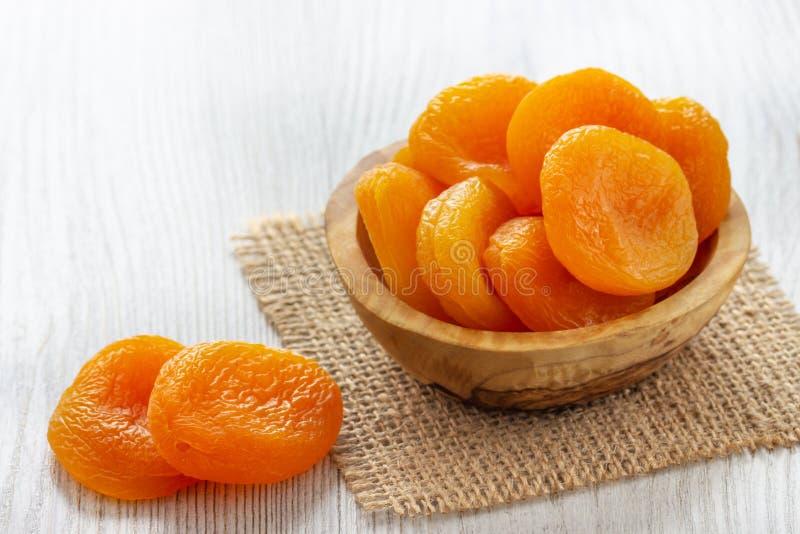 Getrocknete Aprikosen in einer Schüssel auf hellem hölzernem Hintergrund stockbilder