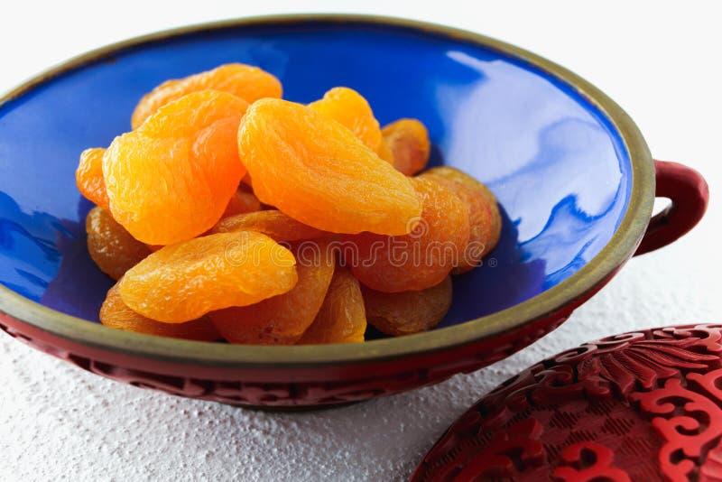 Getrocknete Aprikosen in einer Schüssel mit weißem Hintergrund stockfotos
