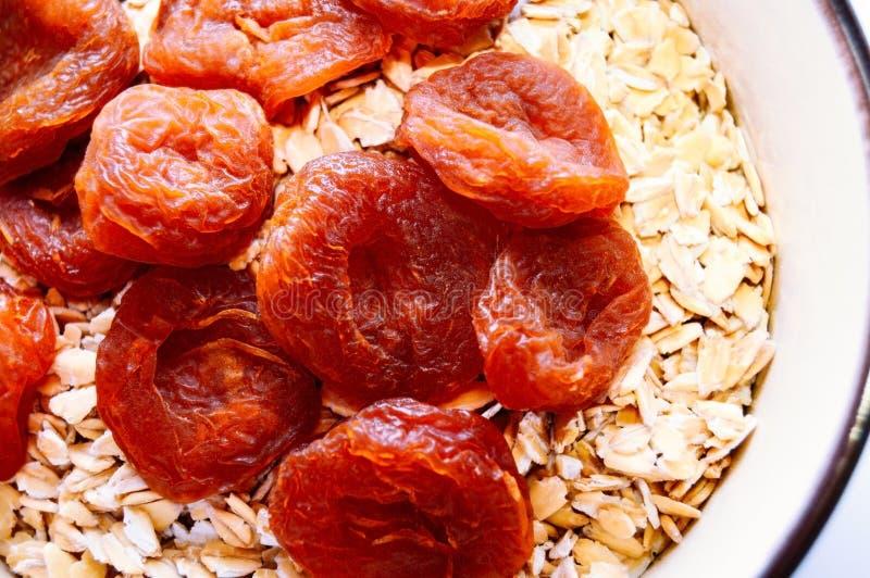 Getrocknete Aprikosen und Hafermehl in einer Schüssel Beschneidungspfad eingeschlossen Nahaufnahme lizenzfreies stockbild