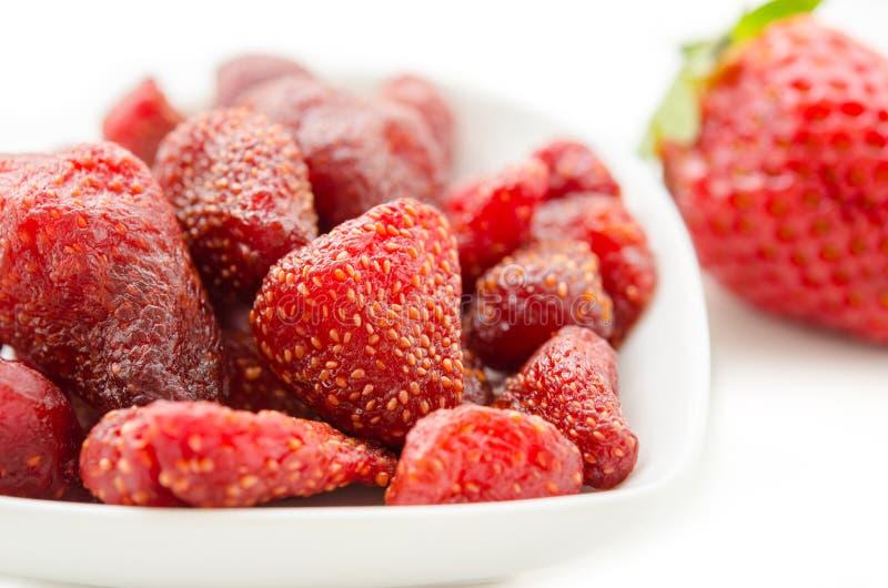 Getrocknete Erdbeeren in der weißen Schüssel und in der frischen Erdbeere stockfoto