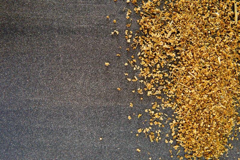 Getrocknete gelbe ältere Blumen auf grauem/grauem Schieferhintergrund lizenzfreie stockfotografie