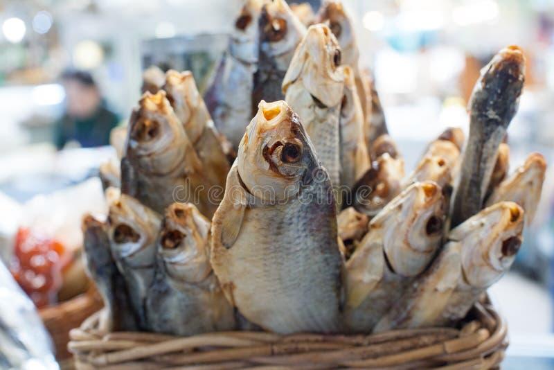 Getrocknete gesalzene Stangenfische im Korbabschluß oben, trockener Wolfsbarschverkauf auf Meeresfrüchtemarkt, geschmackvoller St lizenzfreies stockfoto