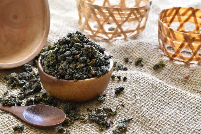 Getrocknete grüne Teeblätter in einer hölzernen Schale auf Sackleinen lizenzfreie stockfotos