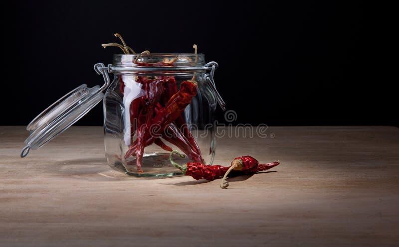 Getrocknete heiße rote Paprikas im Glasglas lizenzfreie stockfotografie