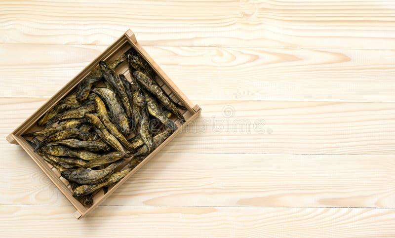 Getrocknete kleine Fische in der Holzkiste auf Weiß Bier-Snack stockfotografie