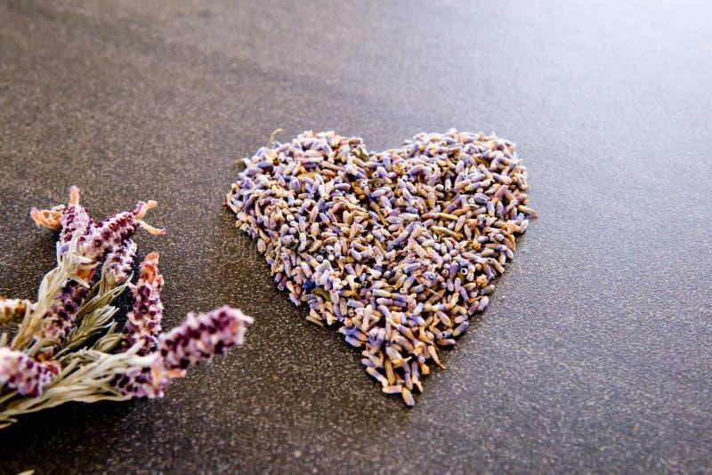 Getrocknete Lavendelblume in der Herzform auf grauem/grauem Schieferhintergrund lizenzfreies stockbild