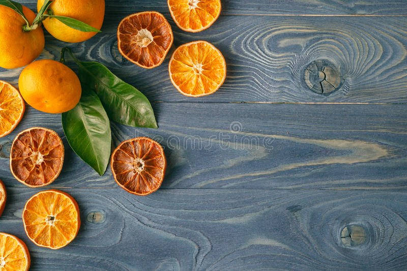 Getrocknete orange Scheiben auf einem blauen Holztisch stockbild