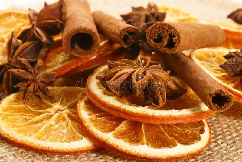 Getrocknete orange Scheiben mit Anis und Zimtstangen auf Jutefaser stockbilder