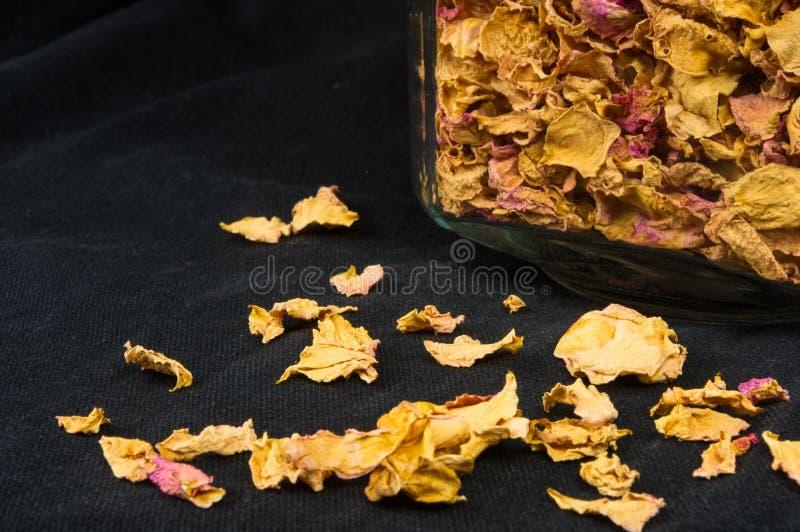 getrocknete rosafarbene Blumenblätter in einem Glasgefäß mit Deckel stockfotos