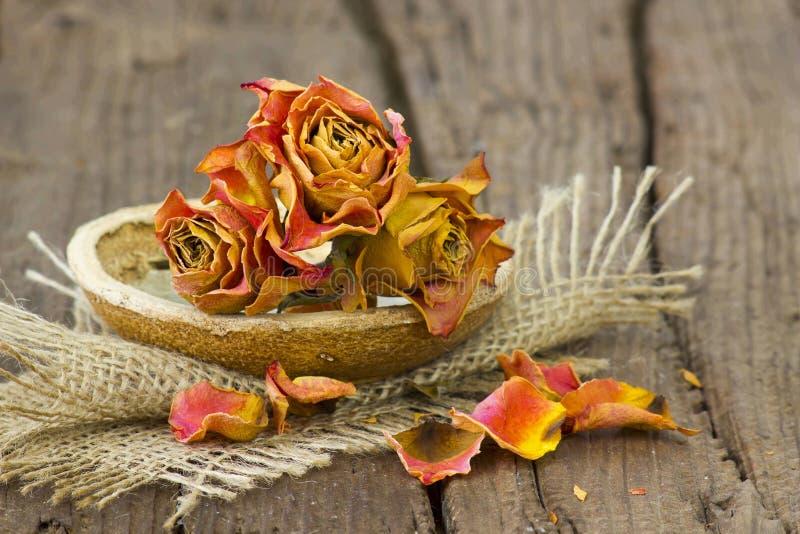 Getrocknete Rosen in der Schüssel auf hölzernem Hintergrund lizenzfreies stockfoto