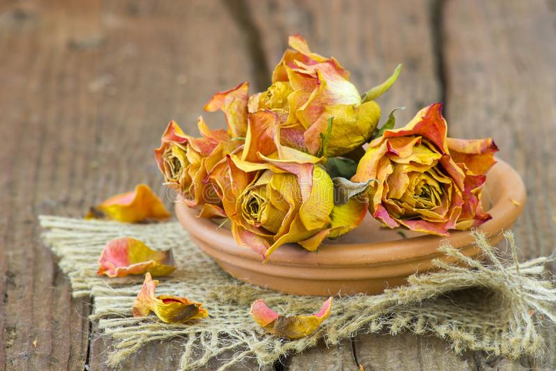 Getrocknete Rosen in der Schüssel auf hölzernem Hintergrund lizenzfreies stockbild