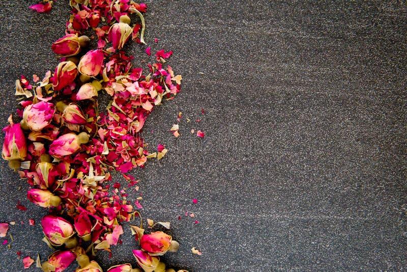 Getrocknete rote Rosen-Knospenblume auf grauem/grauem Schieferhintergrund stockfoto