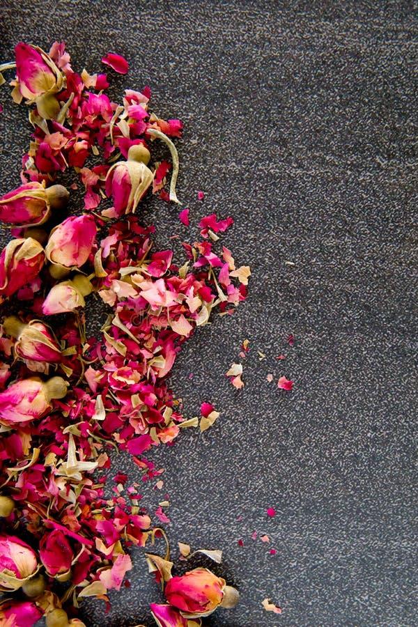 Getrocknete rote Rosen-Knospenblume auf grauem/grauem Schieferhintergrund lizenzfreie stockbilder