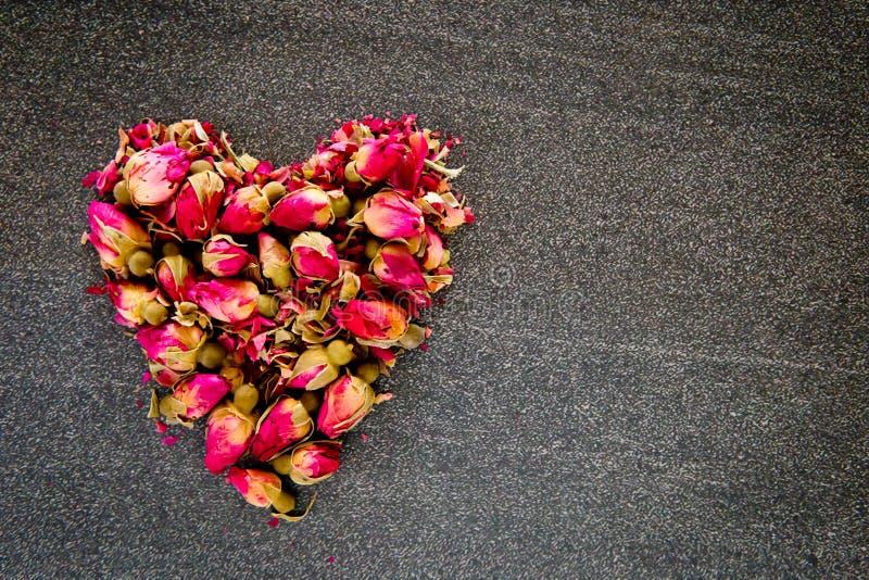 Getrocknete rote Rosen-Knospenblumen in der Herzform auf grauem/grauem Schieferhintergrund stockfotos