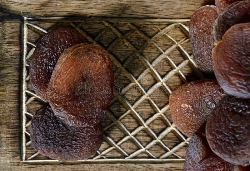 Getrocknete schwarze Aprikosen auf hölzernem Kasten stockbilder