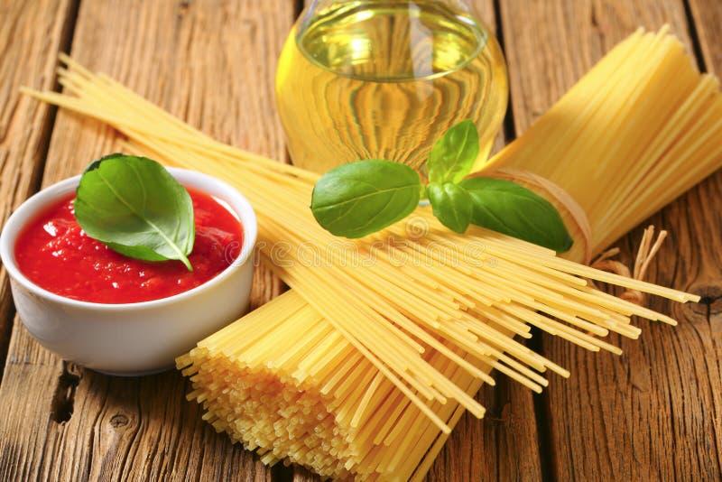 Getrocknete Spaghettis, Tomatenpüree und Olivenöl stockfoto