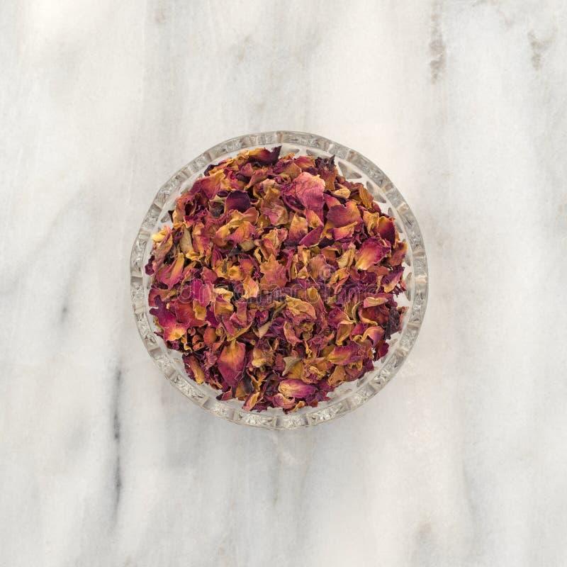 Getrocknete zerquetschte rote Rosebuds und Blumenblätter in einer kleinen Schüssel stockbilder
