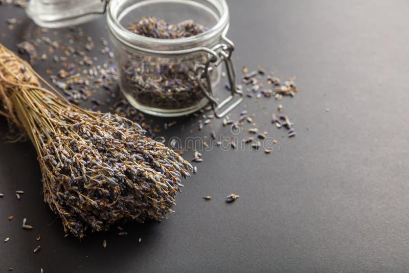 Getrockneter Lavendelblumenstrauß auf schwarzem Tischplattenhintergrund und im Glasgefäß lizenzfreies stockfoto
