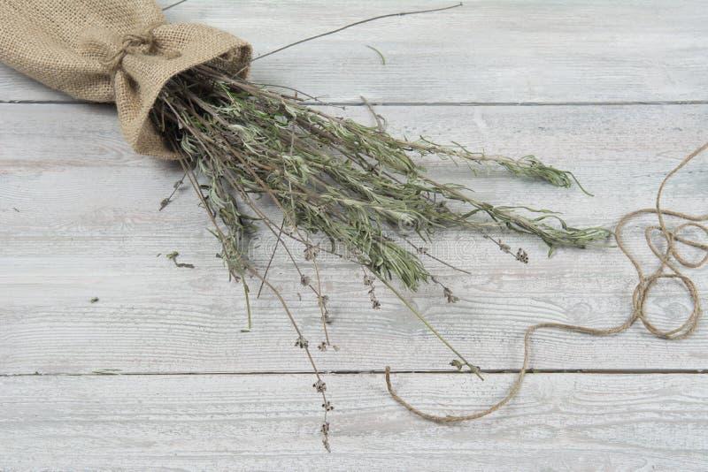 Getrocknetes Lavendelbündel auf dem kleinen Sack und der Weidenplatte auf dem Holztisch Schablone für die Werbung lizenzfreie stockfotos