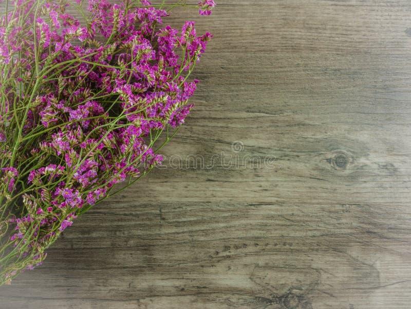 Getrocknetes Rosa, purpurrote Blumen auf hölzernem Hintergrund stockfotos