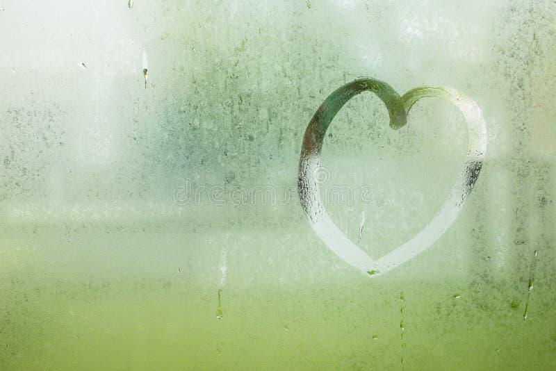 Getrokken hart op waterdaling van regen op vensterglas afgebraamde tuin royalty-vrije stock fotografie
