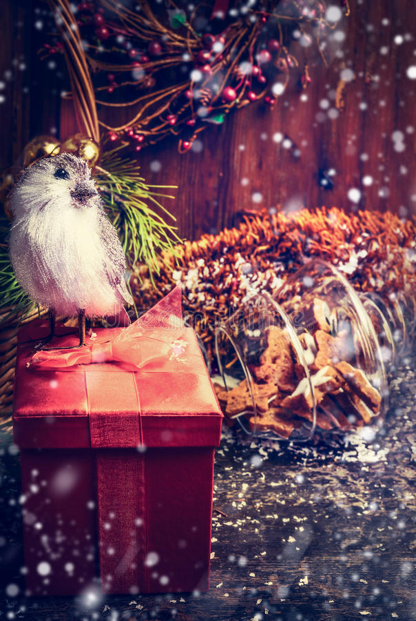 Getrokken Sneeuwkerstkaart met rood Feestelijk Vakje en Koekjes, decovogel op rustieke houten achtergrond stock foto