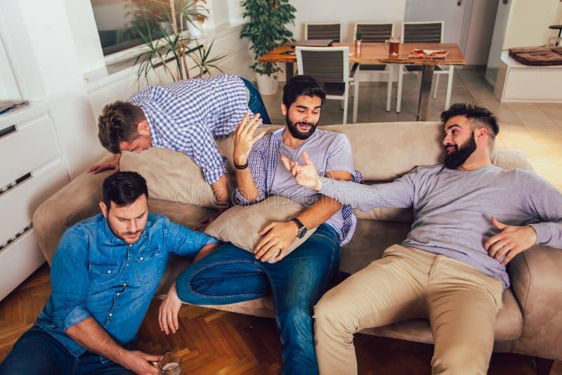 Getrunkene Kerle schlafen nach Nachtereignissen auf dem Boden und dem Sofa in der unterschiedlichen Haltung im Wohnzimmer stockfotos