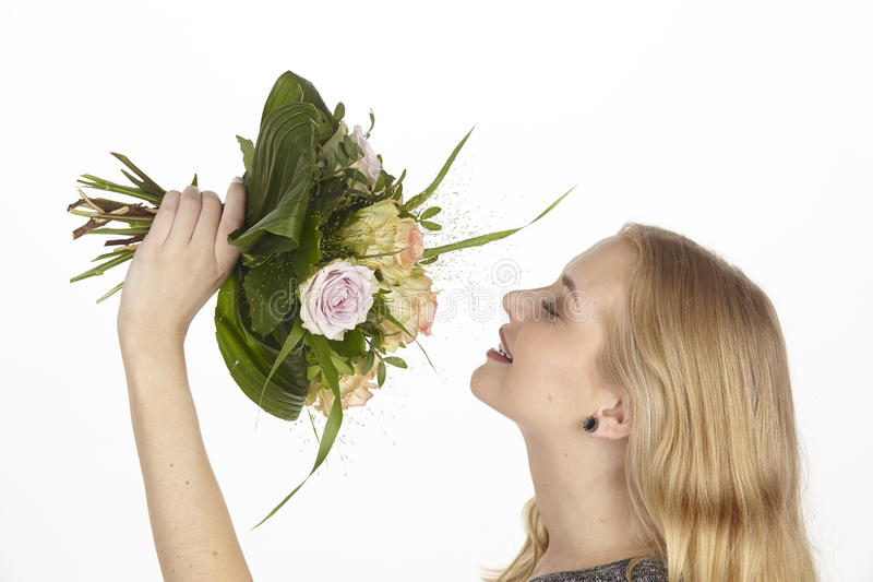 She gets a bouquet of flowers (roses) fpr birthday. A young attractive blond woman gets a bouquet of flowers (creamy and yellow roses) for her birthday stock photos