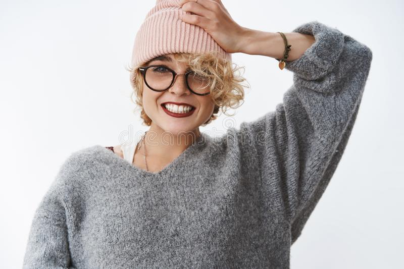 Getting all trendy this winter season. Portrait of charming blond european girlfriend in sweater and pink beanie pulling royalty free stock image