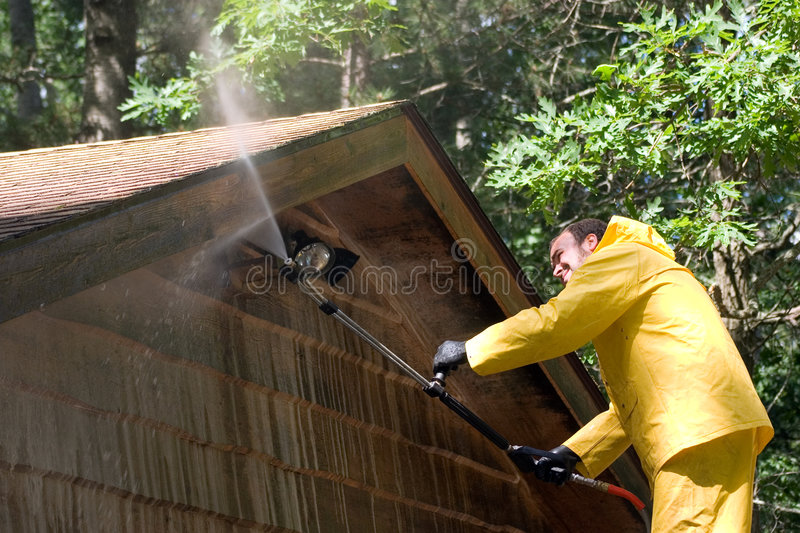 Getting It Clean. A man pressure washing a garage stock images