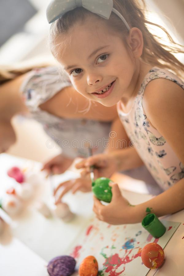 Getting creative with paint. Little girls coloring Easter egg stock photos