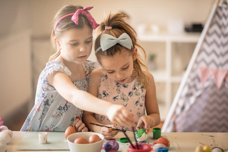 Getting creative together. Little girls coloring Easter egg royalty free stock images