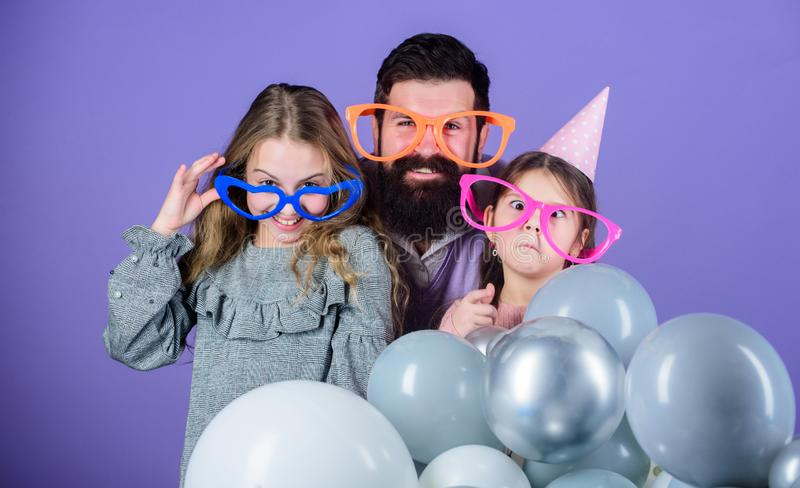 Getting funny. Family of father and daughters wearing party goggles. Father and girl children enjoying party time. Happy royalty free stock image